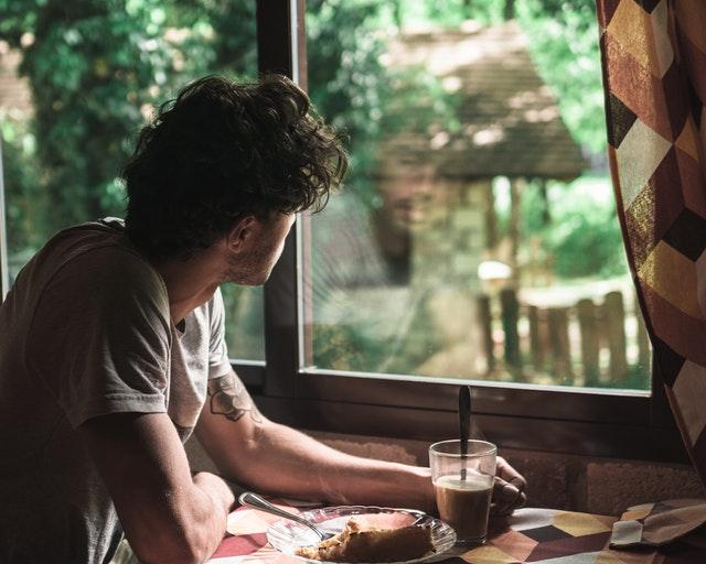 Muž s kávou pozerajúci sa cez okno