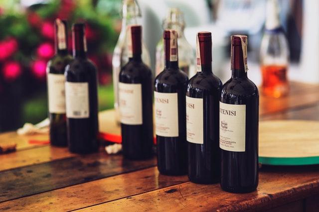 Vínové fľaše s vínom položené na stole.jpg