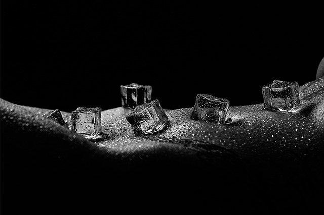 Nahé ženské telo pokrytí kvapkami vody s kockami ľadu.jpg