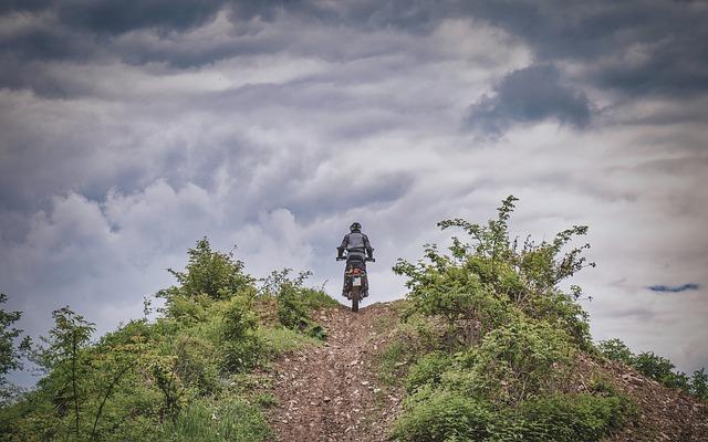 Muž na motorke, jazdí na kopci v prírode.jpg