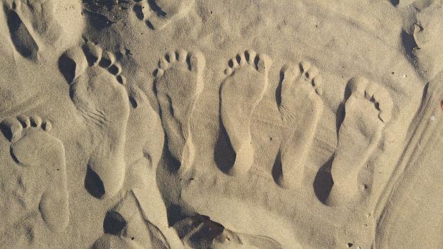Odtlačky malých a veľkých chodidiel v piesku.jpg