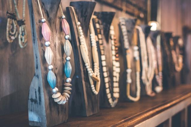Farebné náhrdelníky zavesené na stojanoch v obchode