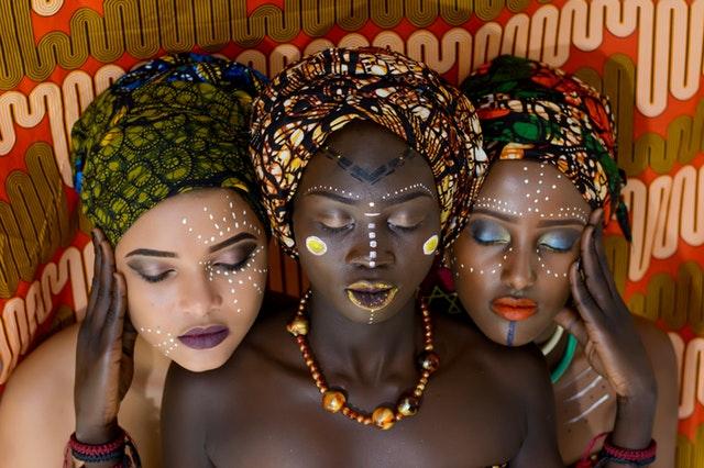 Tri ženy s pomaľovanými tvárami a výraznými šperkami