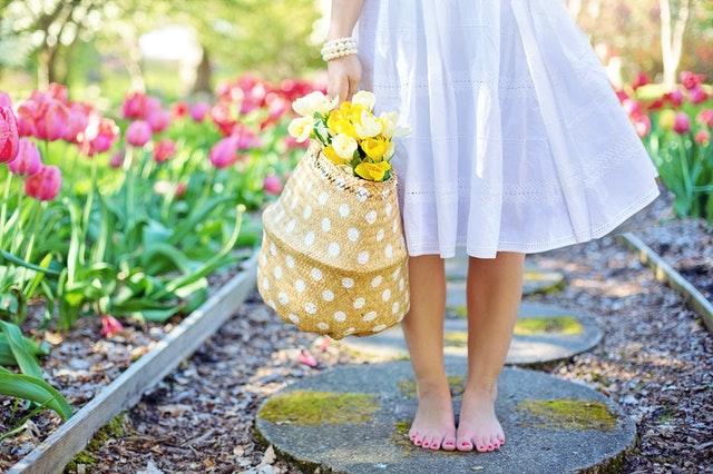 Bosá žena s košíkom s kvetmi stojí na chodníku