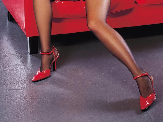 Ženské nohy v silónkach a červených topánkach na podpätku