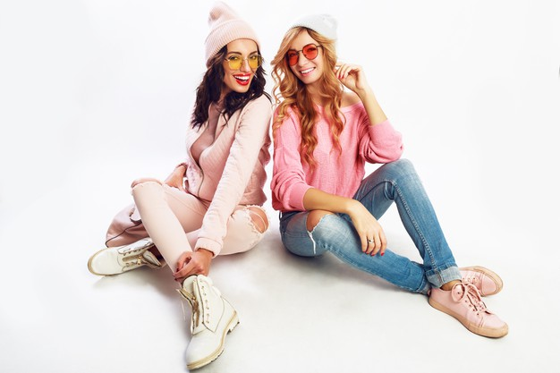 two-laughing-girls-best-friends-posing-studio-white-background-trendy-pink-winter-outfit_273443-3638
